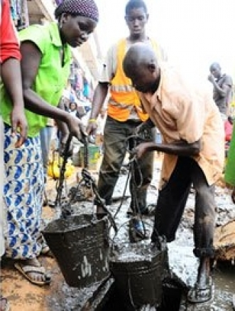 Cleaning. Residents scoop sewage from a